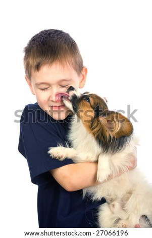 A little dog licking a young boy's nose