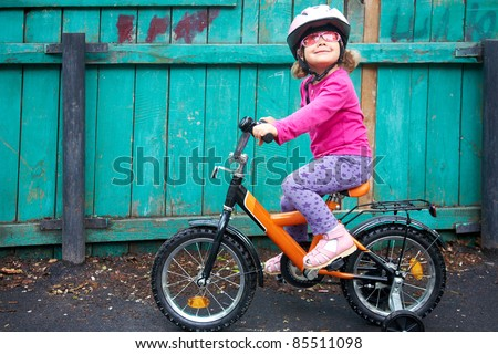 A little dreamy girl in pink glasses riding a bicycle in slums