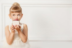 A little fashion-girl with a hairstyle, make-up and red nails looks in a mirror on a white background