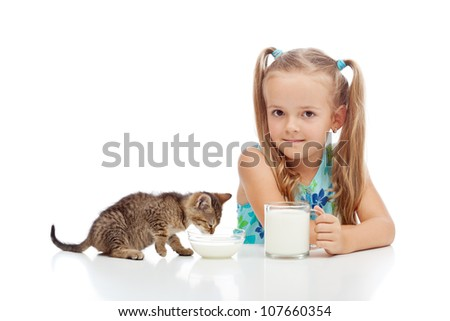 A little fresh milk for the little ones - girl and her kitten drinking, isolated