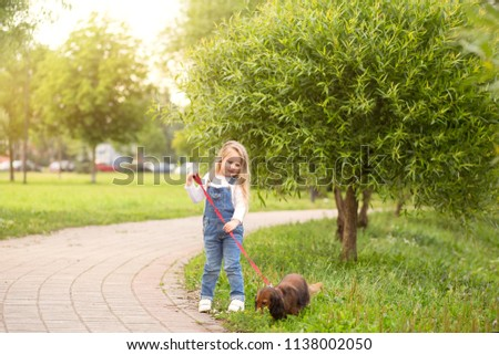 a little girl, a blonde, walks with her dog dachshund in the city park. A healthy time for children