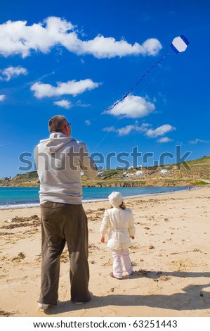 A little girl and dad run a kite in the sky with clouds on the beach near the sea
