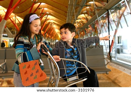 A little girl and her brother awaits for their flight departure at the departure lounge of an airport.