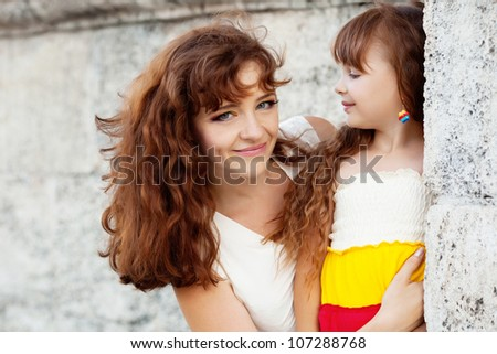 a little girl and her mother standing near the wall