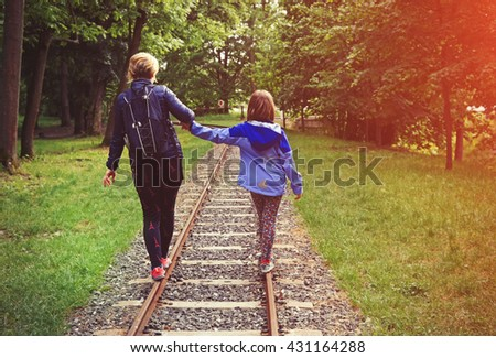 Stock Photo a little girl and his mother balancing on the rails.