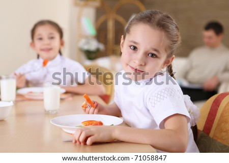 a little girl at home having meal and her family on the background - stock photo