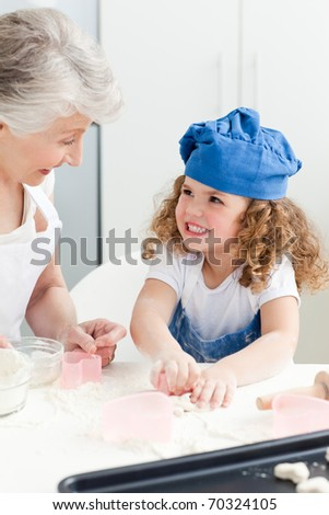 A little girl baking with her grandmother at home