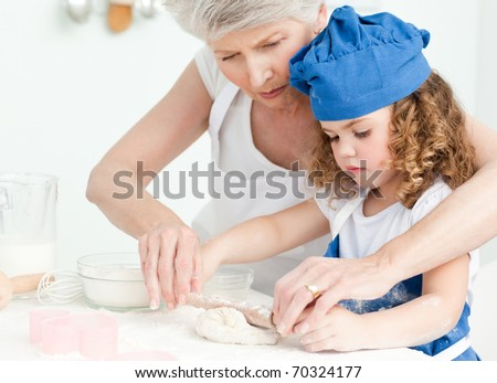 A little girl baking with her grandmother at home - stock photo