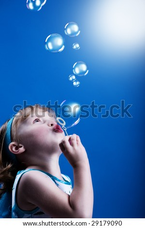 a little girl blowing soap bubbles
