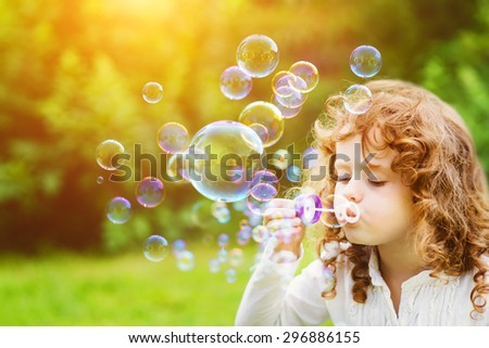 A little girl blowing soap bubbles in summer park. Background toninf for instagram filter. #296886155