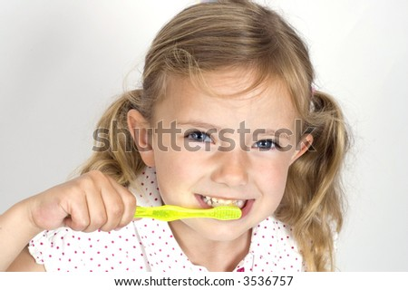 A little girl brushing her teeth with a brightly colored toothbrush