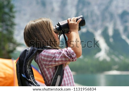 A little girl camping, exploring the nature around her with binoculars. The girl is wearing a hiking backpack. Concept of: curiosity, research, exploration, campsites for children.