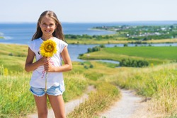 A little girl child holds a sunflower flower with a view of a mountain landscape with fields and river