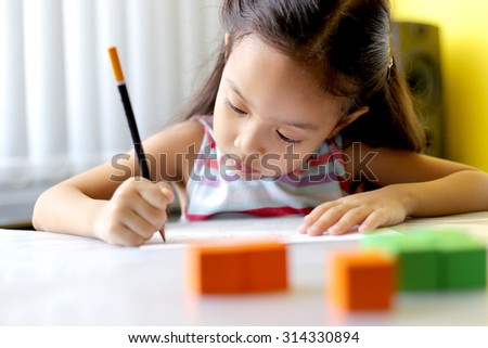 A little girl concentrates her learning at school - Shallow depth of field focusing on the eyes