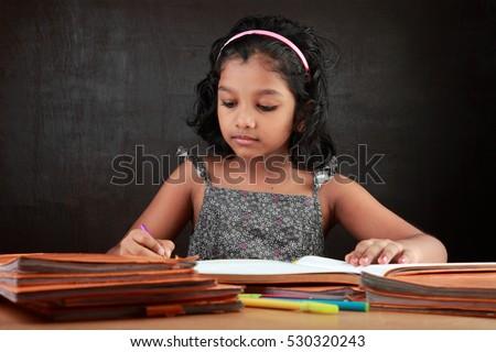 a little girl does her homework ...