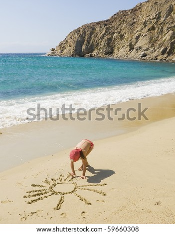 A little girl draws a sun on the sand near the sea - stock photo
