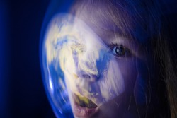A little girl dreams of becoming an astronaut and flying into space. conquering the cosmos. children's dreams. reflection of the planet on the glass of the spacesuit, helmet.