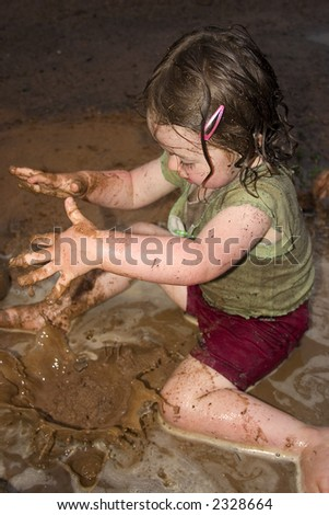 a little girl dropping mud into a puddle