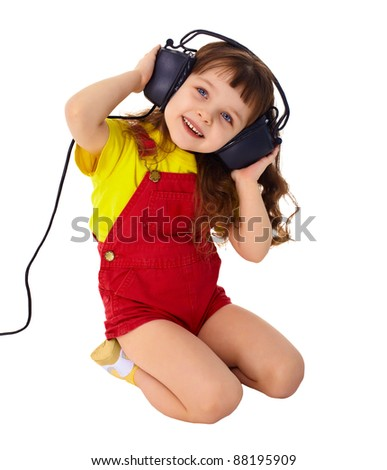 A little girl enjoys music in big headphones isolated on white background