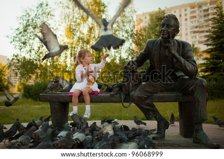 a little girl feeding the pigeons in the park near the statue