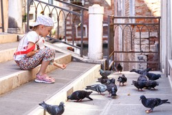 A little girl feeds pigeons. The girl is sitting on the stairs. The girl in the cap. A child in Venice. Birds eat the bread. To share food. Love nature. Help the weak. One in the city.
