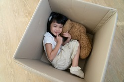 a little girl hide in cardboard box play hide and seek game having fun with parent in moving day to new house, asian family playful happy together concept.