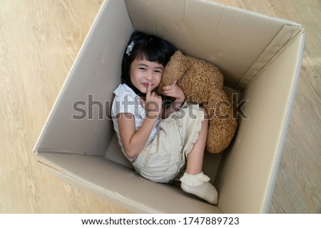 a little girl hide in cardboard box play hide and seek game having fun with parent in moving day to new house, asian family playful happy together concept. Stock photo ©