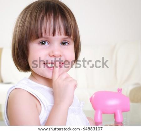 A little girl hides her money in the pig piggy bank.