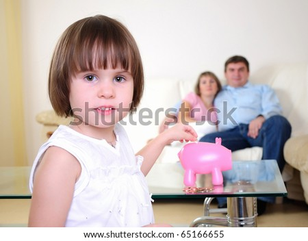 A little girl hides her money in the pig piggy bank.