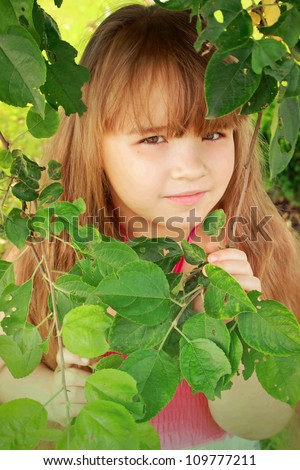 A little girl hiding behind a tree - stock photo