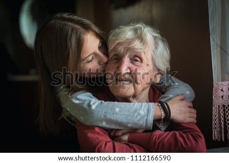 A little girl hugs her grandmother.