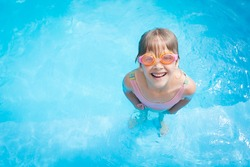 a little girl in a bathing suit and pink swimming glasses swims in a pool with blue water