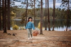 A little girl in a black hat cheerfully walks through the forest. She is holding a basket with yellow leaves. In the background is a forest lake.