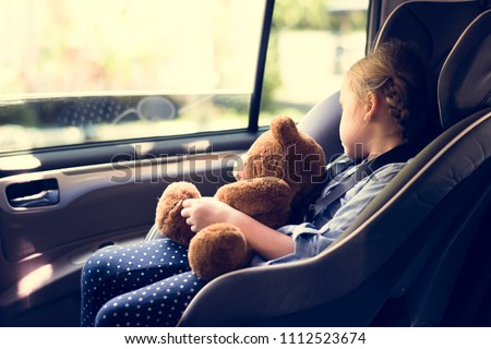 A little girl in a car seat