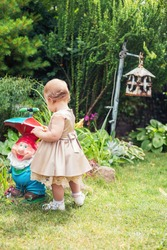 A little girl in a dress stands in the garden near the garden gnome