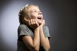 A little girl in a gray dress looks away. Her eyes and mouth are wide open, she is surprised at the surprise.