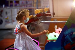 A little girl in a medical mask plays a game machine in the children's room, observing COVID-19 safety measures.
