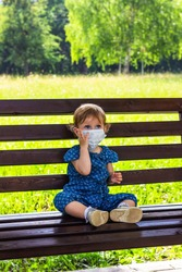 a little girl in a medical mask sits alone on a bench in a summer Park