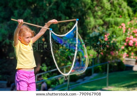 A little girl in a park making huge rope soap bubbles.
