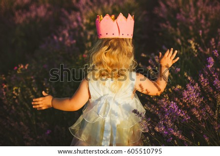 A little girl in a pink felt crown and white dress runs through the lavender field