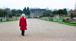 A little girl in a red coat walks alone down a wide gravel path towards a large country house