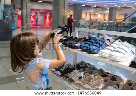 A little girl in a store buys shoes. Shopping, sale.