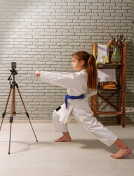 A little girl in a white kimono with a blue belt takes karate lessons via the Internet while at home on self-isolation during quarantine