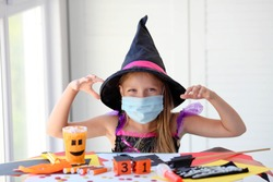 A little girl in a witch costume in a medical mask makes crafts and scares. Halloween with safety measures from Covid-19