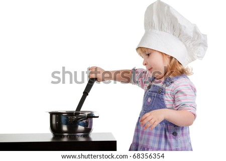 a little girl in cook hat cooks