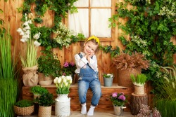 A little girl in overalls sits on porch of wooden house, around green plants and flowers. Gardening. Child playing in backyard. Summer vacation with little girl. celebration concept. Mother's day