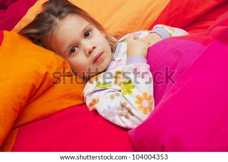 A Little Girl in Pajamas Lying on a Large Bed