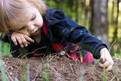 A little girl intently touches lumps of soil, plays and learns the world, lying on the grass in a park or garden. The child is lost in the forest and lies sadly waiting for help and salvation.