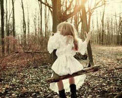 A little girl is alone swinging on an old vintage swing in the woods with trees for a fear, hope or sadness concept