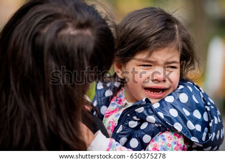 A little girl is crying in her arms. Mothers Day.